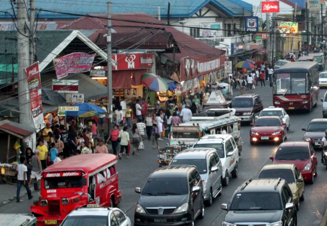 Cars, pedestrians and commerce struggling for a space in Davao