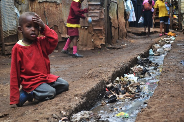 A young boy sits over an open sewer.